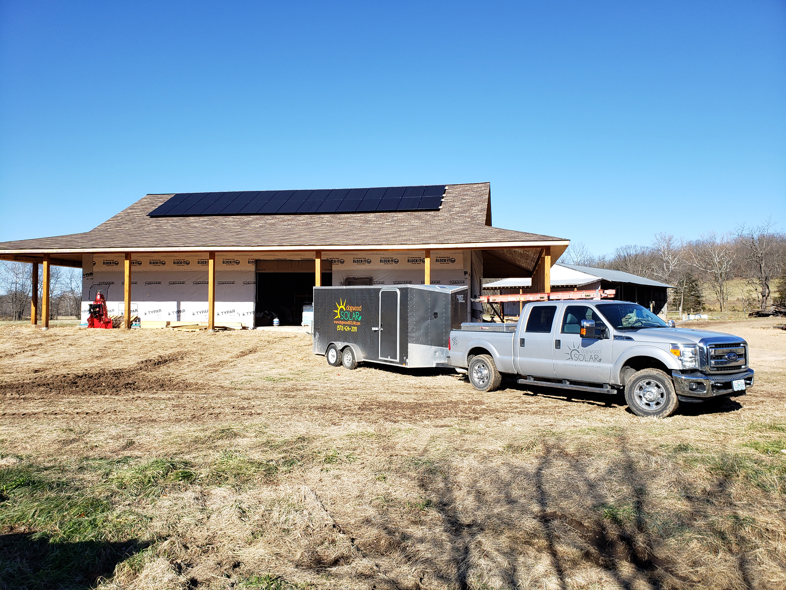 The Dogwood Solar truck and box trailer are parked in front of a home that is under construction. A perfect grid of solar panels are seen on the roof with a blue sky above.