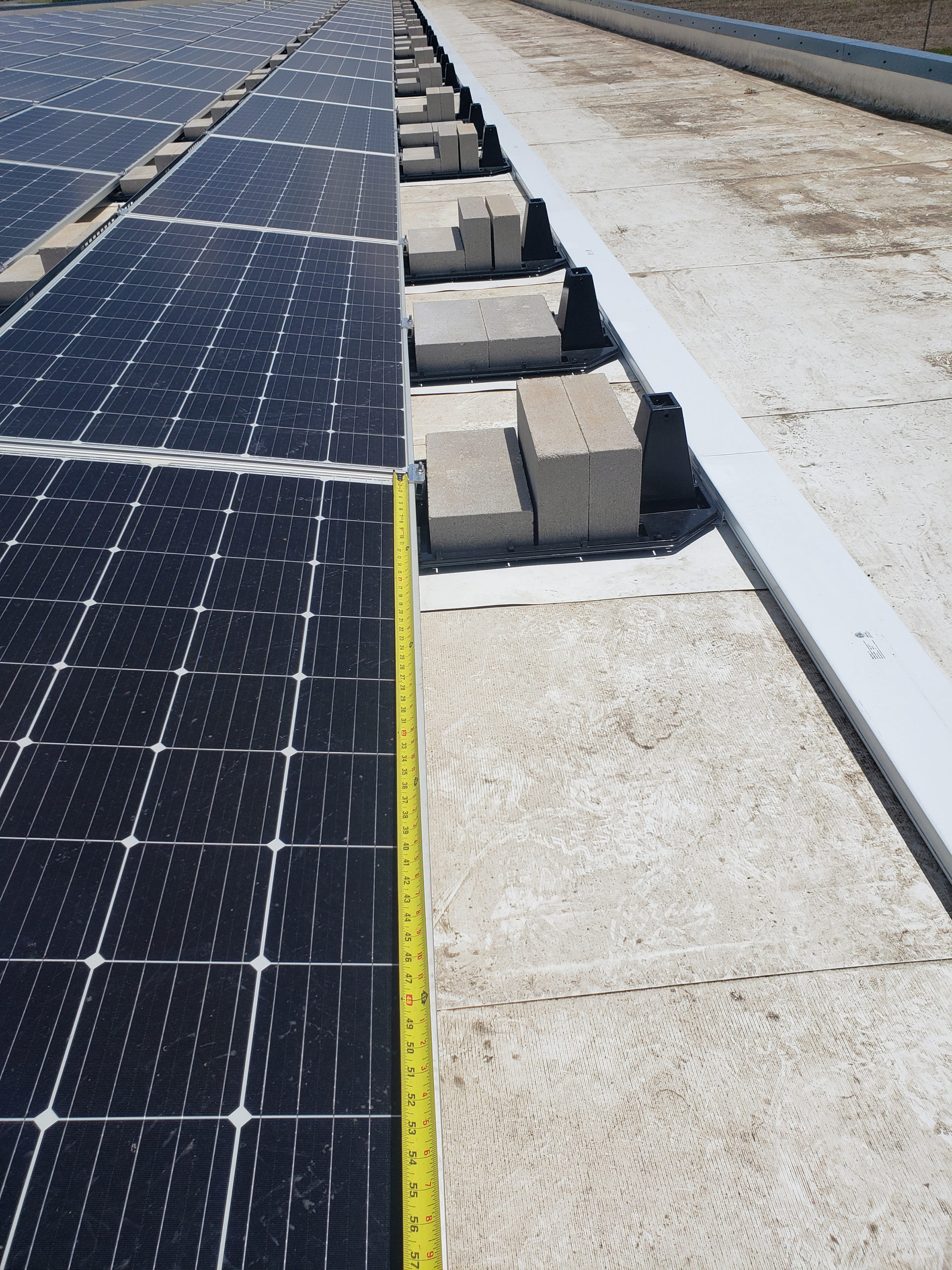 A close up of the solar panel rows ending is seen. A measuring tape stretches over 60 inches along one edge of the panel to showcase the size.