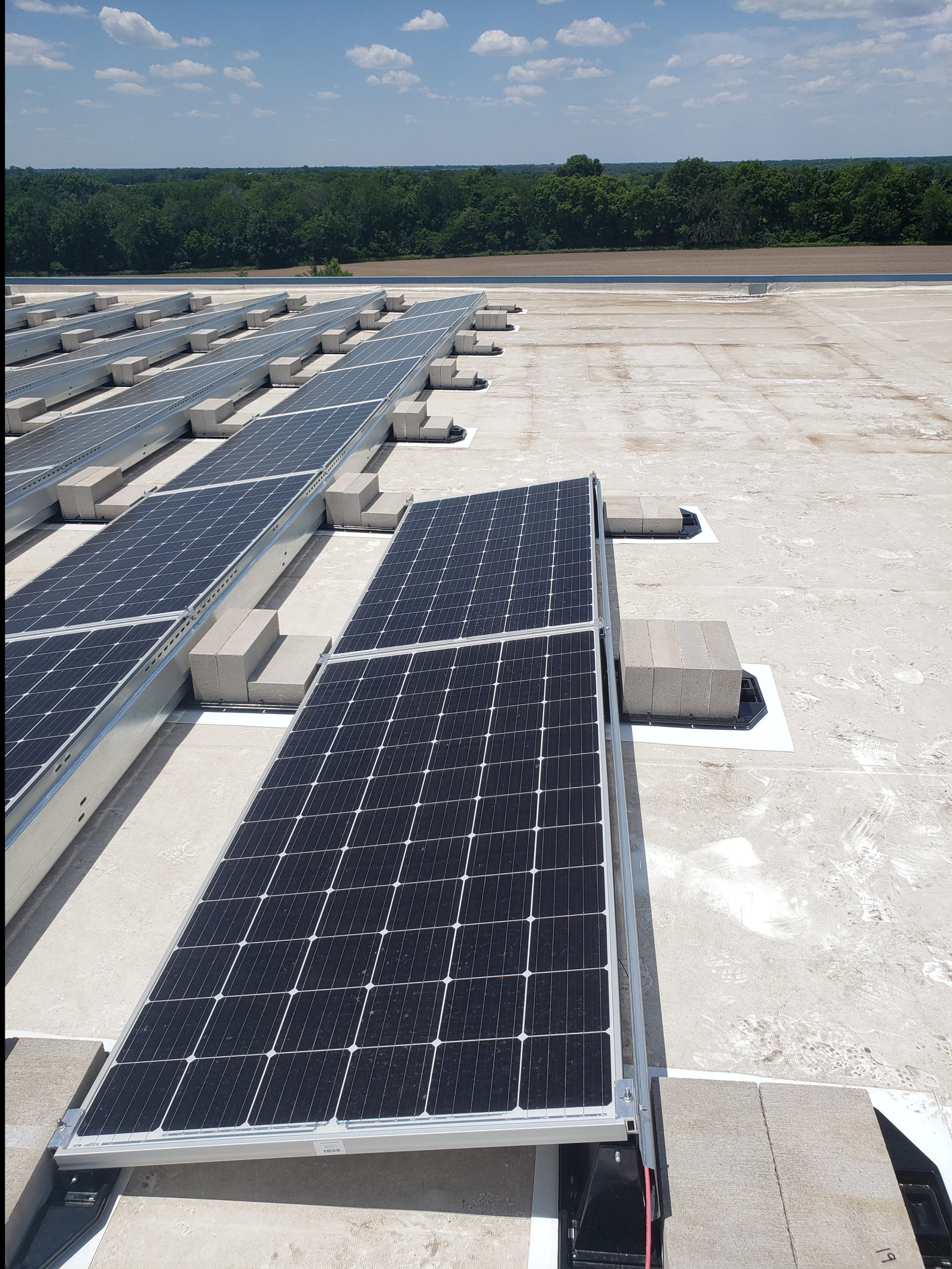 A close up view of the commercial solar system rows is seen from standing on the rooftop. They are brightly lit at the best angle to harness the sun's solar energy.