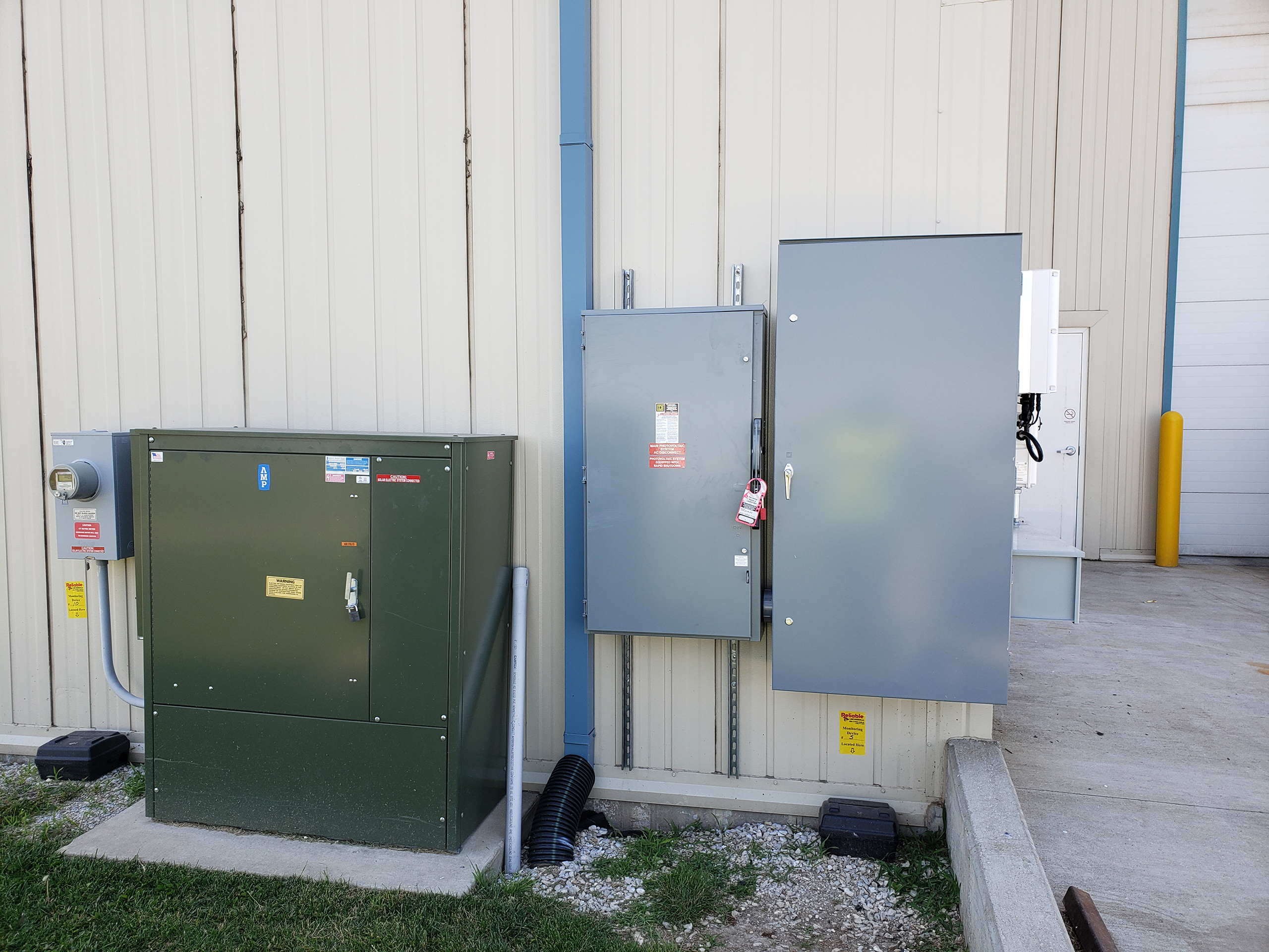 The corner of a commercial building has neatly lined up electrical boxes where the solar system connects.
