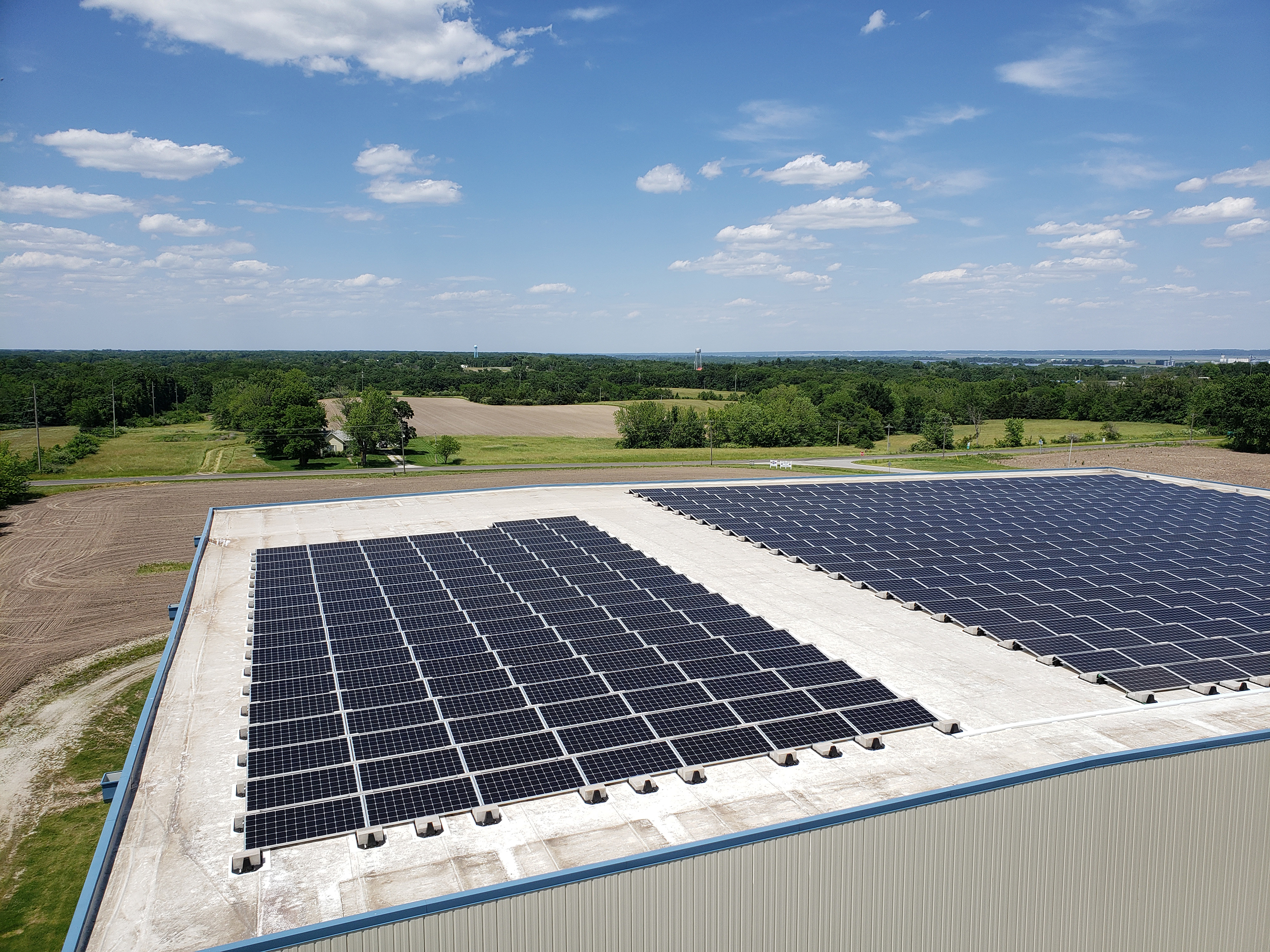A flat commercial roof is covered with solar panels in perfect lines and rows. A walk-way divides the large solar system install. A bright blue sky with a few scattered puffy clouds can be seen with a rural tree line in the distance.