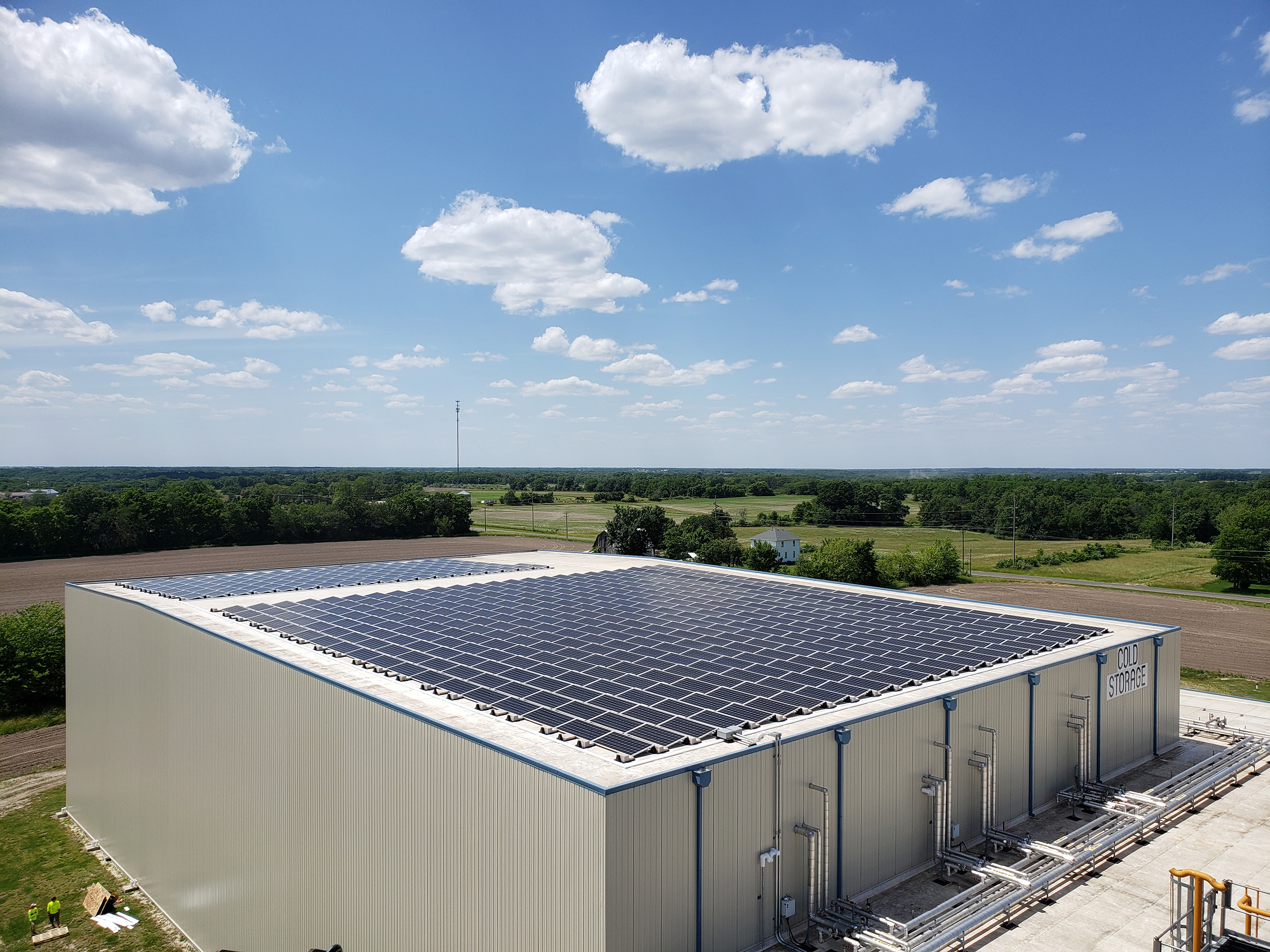 A field of solar panels are seen covering the roof of a large metal commercial building. The sky above is a bright clear blue with a sprinkling of puffy white clouds.