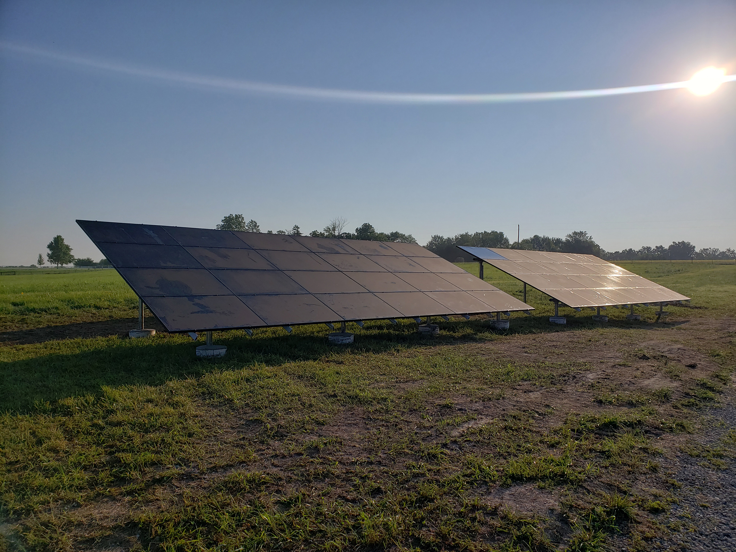 Two large groups of solar panels are seen in a mowed field of grass. The sun is shining in a clear blue sky. A row of trees are seen in the distance behind the solar panels that are mounted at ground level.