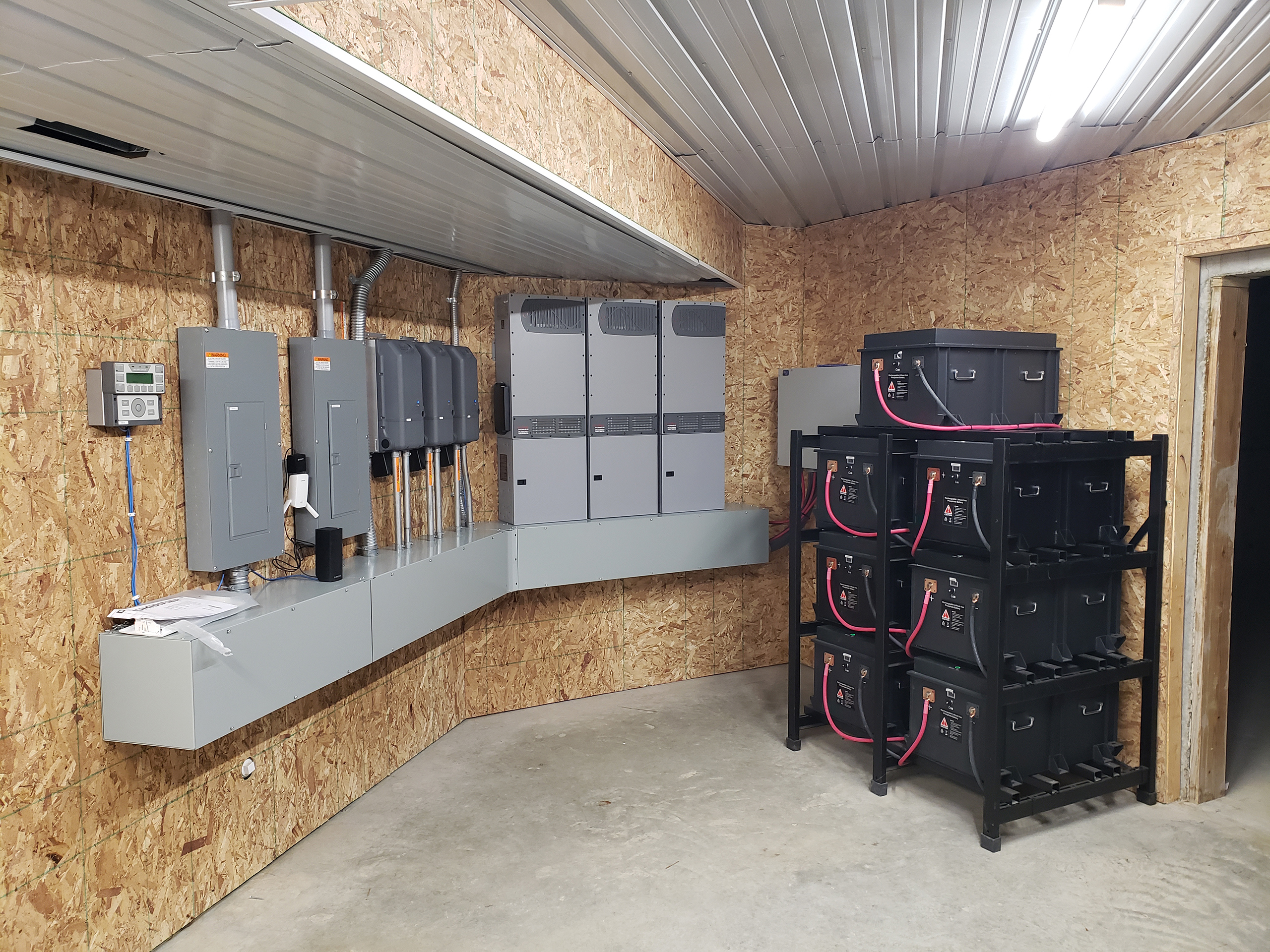A neatly organized battery system is seen in a roomy, albeit unfinished, space. Electric panels and battery system wiring boxes are nicely lined up on the wall. A black rack with large batteries on shelves is against the opposite wall.