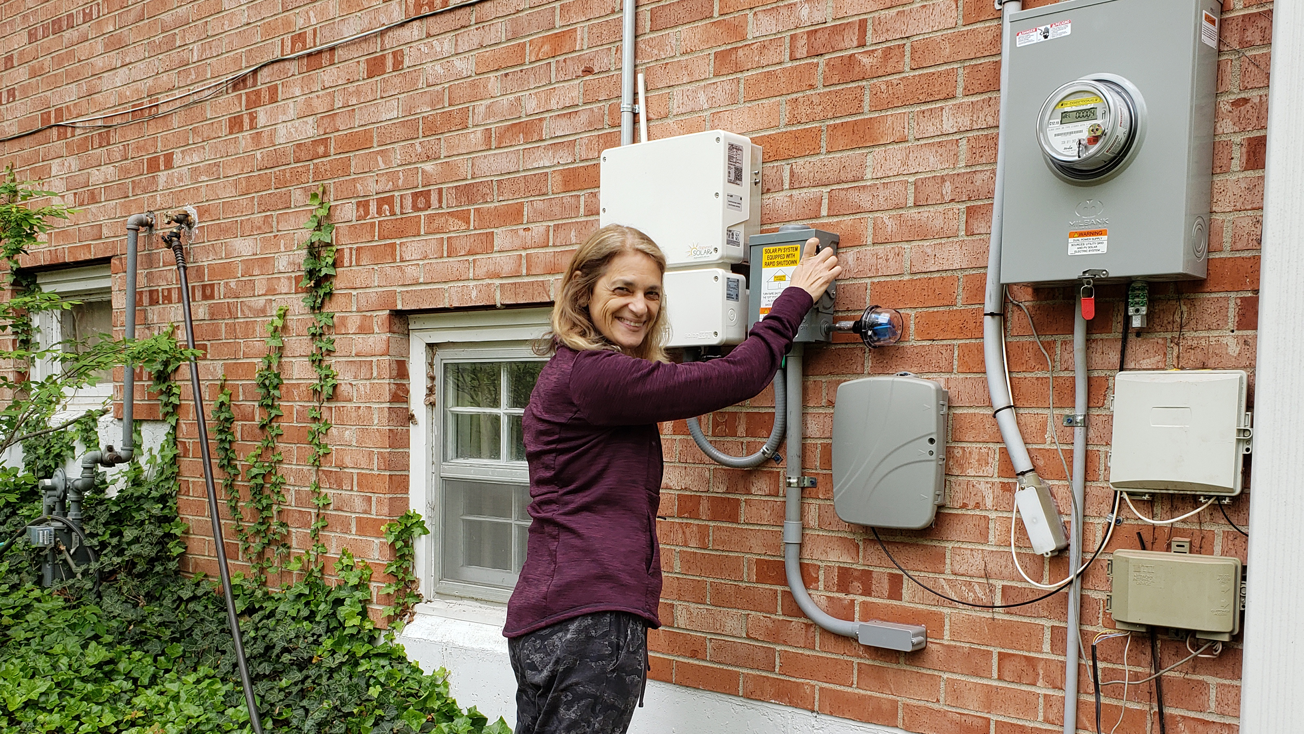 Woman stands posed to flip the switch where the solar system integrates with the utility panel outside a brick home. She is smiling and looking over her shoulder at the camera. Some green vines can be seen to her left, showing it is an established home.