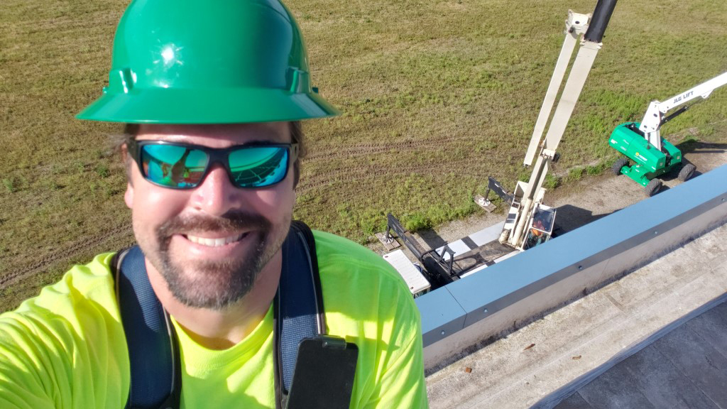 Dan wears a hardhat on a rooftop with equipment in the background.