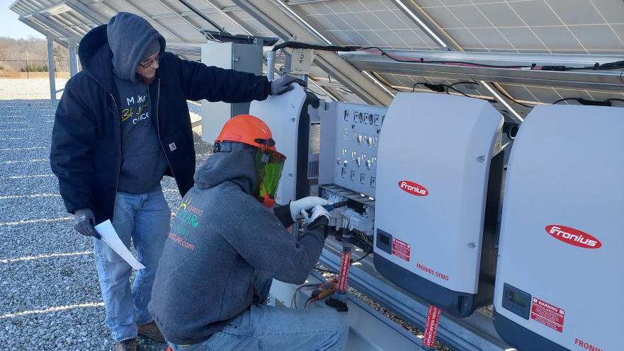 Two Dogwood staff members are working on the large solar system on a commercial rooftop.