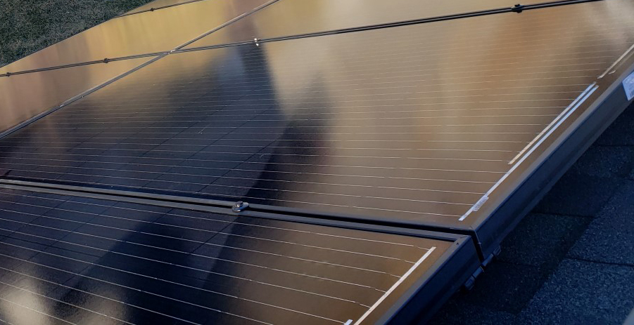 Up close, you can see the texture of the inner-workings of a solar panel. The sleek black finish reflects some surrounding light.